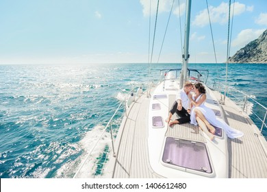 Young Couple Relaxing on a Yacht. Happy wealthy man and a woman by private boat have sea trip
