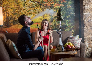Young couple relaxing and smoking hookah