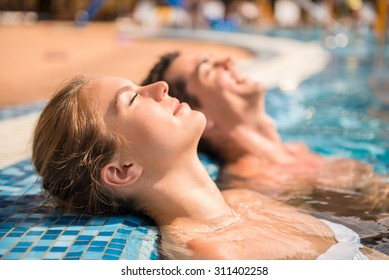 Young couple are relaxing in swimming pool.