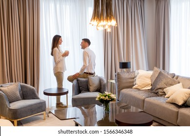 Young couple relaxing and talking with coffee cups in the luxurious room of contemporary apartment