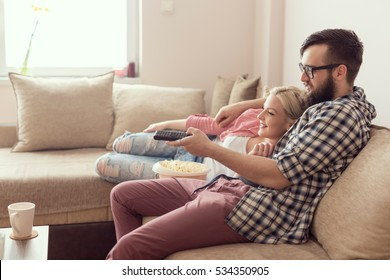 Young couple relaxing in their apartment, lying on the couch, watching a movie and eating popcorn. Lens flare effect on the window, focus on the guy