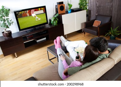 Young couple relaxing, watching TV and having a beer