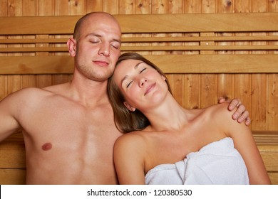 Young couple relaxing in a wooden sauna with their eyes closed