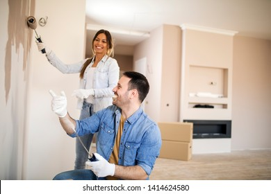 Young couple renovating their apartment painting walls using painting tools while wearing gloves.
