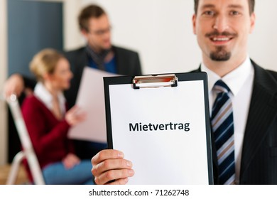 Young couple renting a home or apartment, they are meeting the owner or real estate broker standing in front (the sign is written in German)
