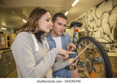 young couple repairing a bike with a tablet