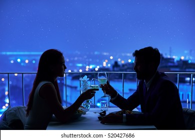 Young couple at restaurant having dinner. Silhouette