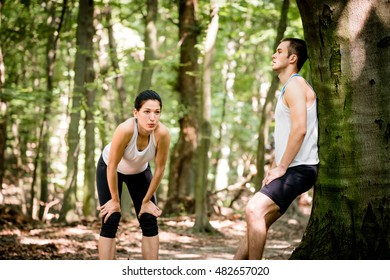 Young couple resting after jogging in nature, man leans against tree