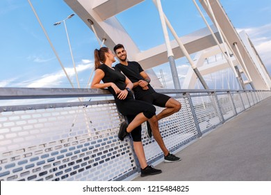 Young couple resting after workout outdoors.
