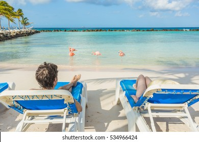 Young couple resting with flamingos on the background. Flamingo beach in Aruba.