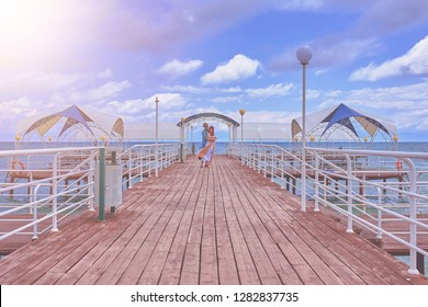 Young couple resting on the beach on their honeymoon. Man and woman hugging on the pier at sea