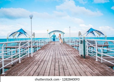 Young couple resting on the beach on their honeymoon. Man and woman holding hands on pier at sea
