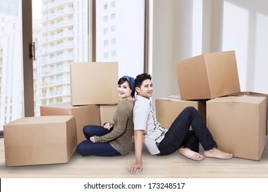 Young couple resting while moving into a new home.