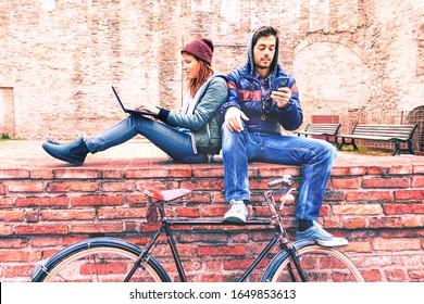 Kleines Paar mit Retro-Fahrrad mit Telefon und Laptop - Teenager, die Mobilgeräte halten, die im Winter an der alten Stadtmauer sitzen - Videofilme des Lifestyle-Konzepts Bild