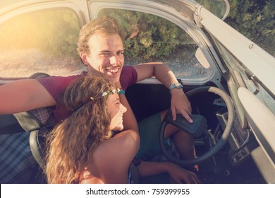 Young couple in a retro car  at sunset, retro style.
