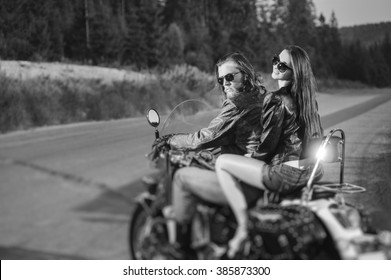 Young couple riders sitting together on shiny custom made cruiser motorcycle. Guy and girl wearing leather jackets and sunglasses on a sunny day. Side view. Tilt lens blur effect. Black and white