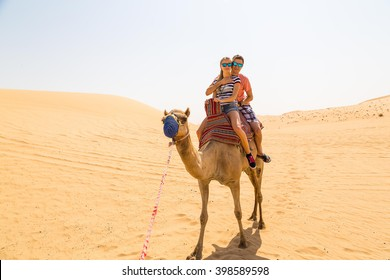 Young couple riding a camel in the middle of a desert near Abu Dhabi