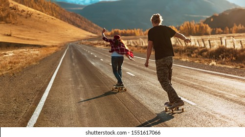Young couple is riding on longboards by straight mountain road at sunset light