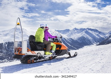 Young couple riding snowmobile snow mountain road