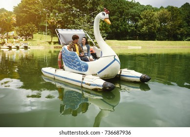 Young couple riding swan boat in park lake