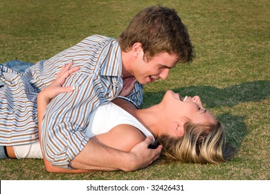 A young couple roll in the grass in the late afternoon sun.