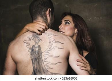 Young couple in romantic hug.Big tattoo on man back