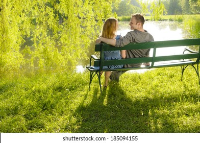 A young couple is romantic in the park on a lake on the go. They sit in the evening light on a park bench and look at a lake.
