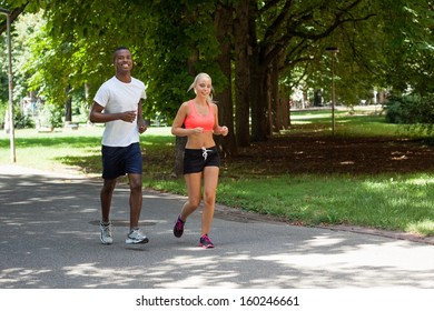 young couple runner jogger in park outdoor summer sport lifestyle