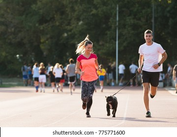 Young couple runnig with french bulldog  at sport field