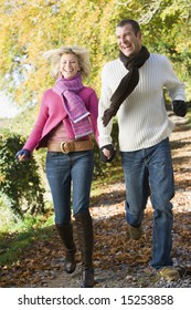 Young couple running along autumn woodland path