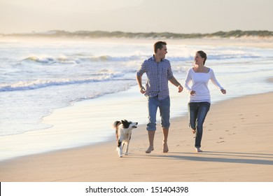 Young couple running along the beach with their dog.