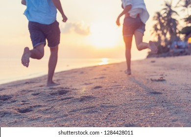 Young couple running along the sandy seashore in the rays of sunset, blurred image perfect background for travel agencies, honeymoon vacation travel in the tropics. Valentines day