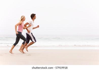 Young Couple Running Along Winter Beach
