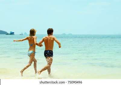 Young couple running to the blue sea