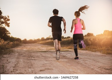 Young couple running at forest trail. stretching before fitness training session at the park. Healthy young warming up outdoors,hi key.