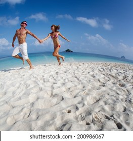 Young couple running on the sandy beach