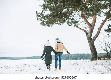 Young couple running on a snowy winter field near a big old pine