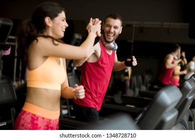 Young couple running on treadmills in modern gym