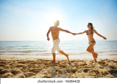 Young couple running on a tropical beach at sunset
