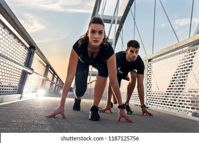Young couple running outdoor on bridge. They are at start position.