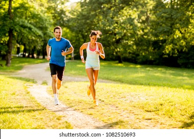 Young couple running outdoors in the park on a sunny day