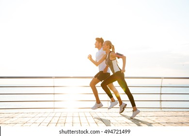 Young couple running over wooden pier at sunset
