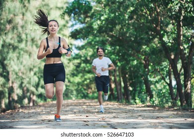 Young couple running in the park.