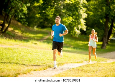 Young couple running in the park on a summer day