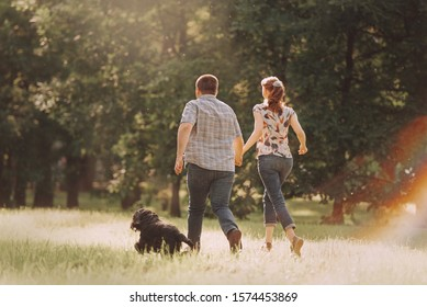young couple running in the park with their dog