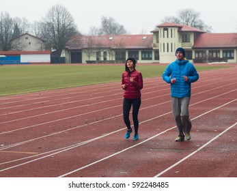 Young couple running in sport outfit otdoors.