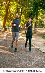 Young couple running together on the jogging track through the forest. Training outdoors