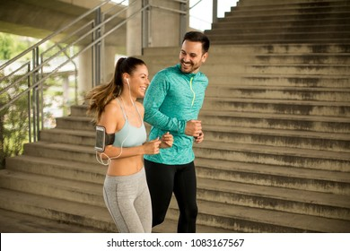 Young couple running in urban environment at sunny day
