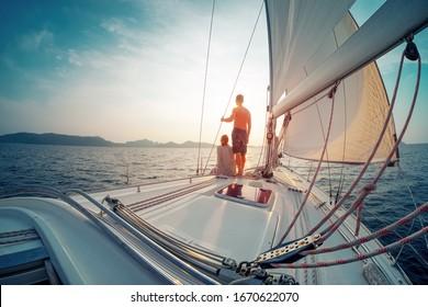 Junge Paare, die bei Sonnenuntergang im tropischen Meer auf ihrer Yacht segeln