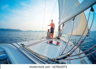 Junge Ehepaare segeln bei Sonnenuntergang im tropischen Meer auf ihrer Yacht. Kippverschiebungseffekt angewendet